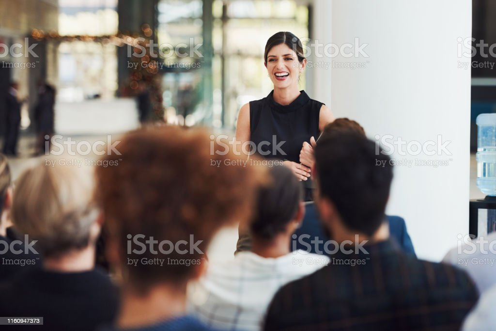 Stay current with trends by learning from powerful speakers Shot of a young businesswoman delivering a speech during a conference Public Speaker Stock Photo