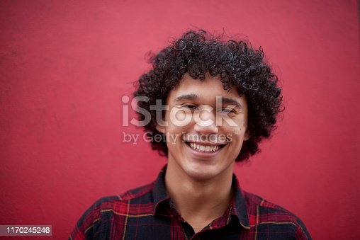 Cropped shot of a handsome young man posing against a red background