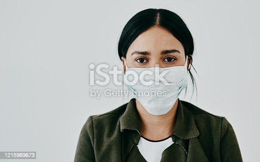 Portrait of a young woman wearing a mask against a grey studio background