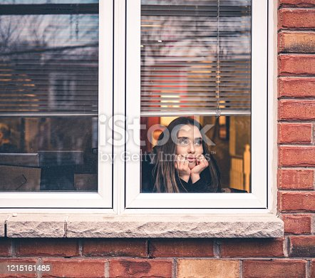 Young woman sitting inside her home, close to the window looking out. She is practicing social distancing due to pandemic of COVID-19 and stay at home order.