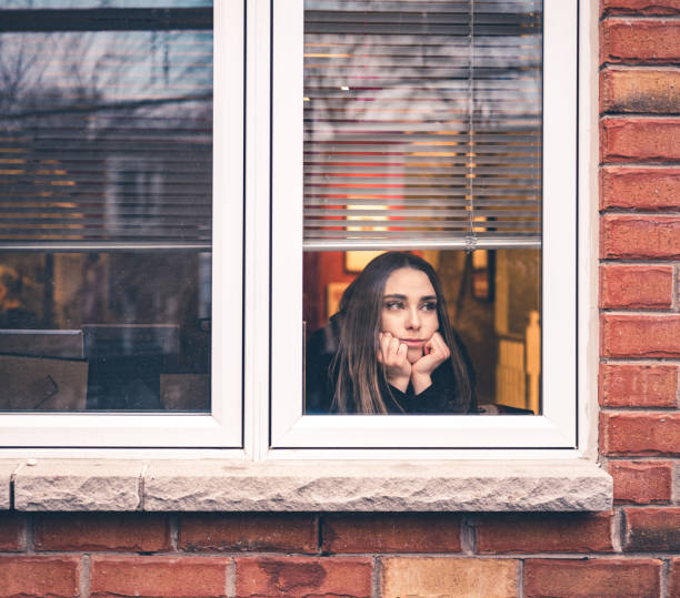 COVID-19, stay home Young woman sitting inside her home, close to the window looking out. She is practicing social distancing due to pandemic of COVID-19 and stay at home order. quarantine stock pictures, royalty-free photos & images