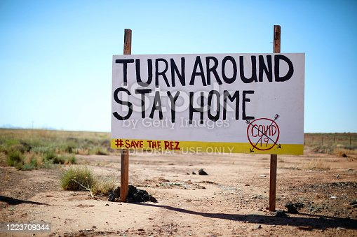 A sign along the road from Leupp to I-40 encourages people in the Navajo Nation to stay at home. COVID-19 hit the nation's rural people particularly hard. May 5, 2020.