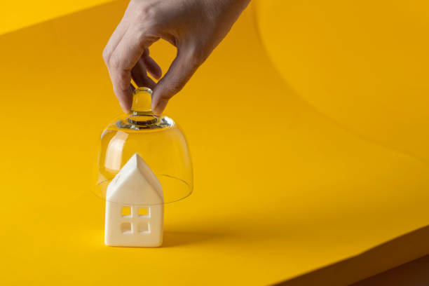 Stay home stay safe  concept. Hand put crystal top for protect the house on yellow background. Lockdown during a viral pandemic concept. stay at home order stock pictures, royalty-free photos & images