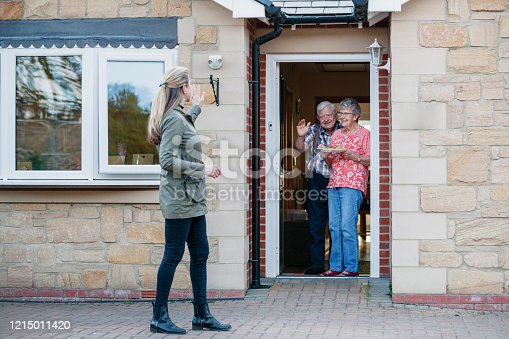 Caucasian female stands back waving from the front door of a bungalow after delivering food, to a senior couple and they wave from their doorway.