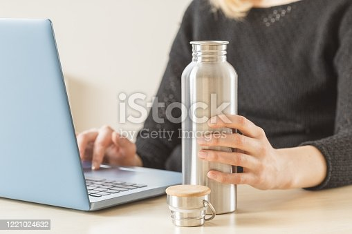 White woman holding her personal stainless steel water bottle on the working table. Daily hydration habit to stay healthy