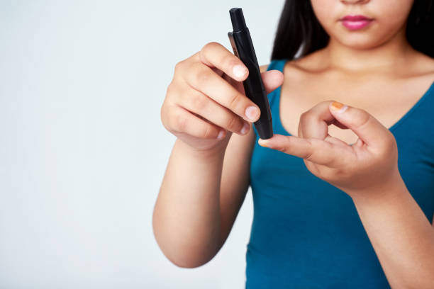 Stay in the know and knock that diabetes Studio shot of a young girl using a blood sugar test on her finger against a gray background hypoglycemia stock pictures, royalty-free photos & images