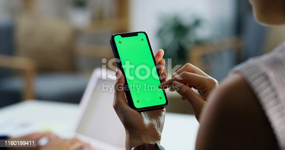 Closeup shot of an unrecognisable businesswoman using a cellphone with a green screen in an office