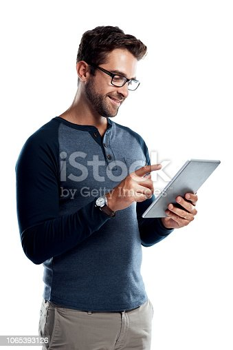Studio shot of a handsome young man using a digital tablet against a white background
