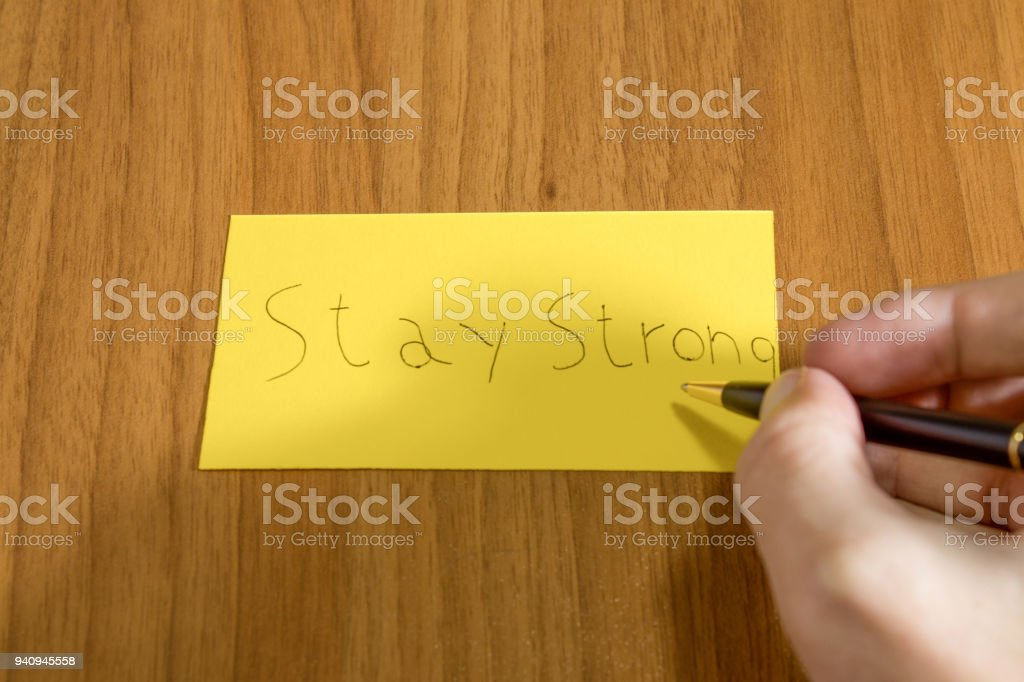 Stay strong handwrite on a yellow paper with a pen on a table composition stock photo