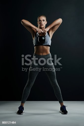 Studio portrait of a fit young woman working out with a kettle bell against a dark background