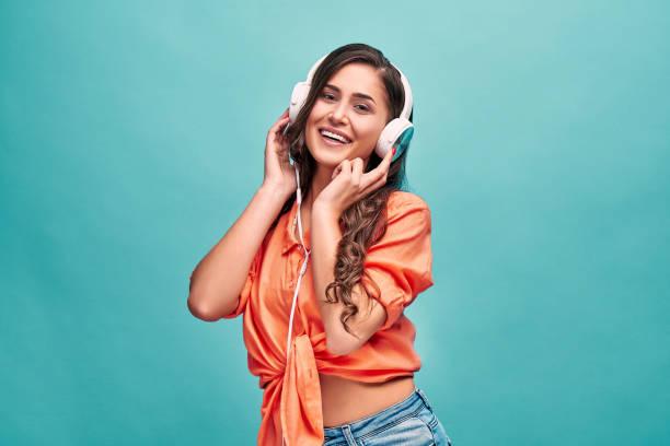 håll ögonen öppna för musik! vacker ung kvinna klädd i orange skjorta håller vita hörlurar med händer och skrattar på blå bakgrund. - stay tuned bildbanksfoton och bilder