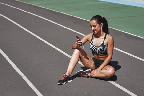 håll ögonen öppna. löpare sitter på stadionspåret. kvinna sommar fitness träning. jogging, idrott, hälsosamt aktivt livsstils koncept - stay tuned bildbanksfoton och bilder