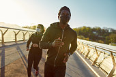 istock Staying active during quarantine. Young african athletic family in medical masks running on the bridge during a pandemic. Sport during quarantine 1248798065