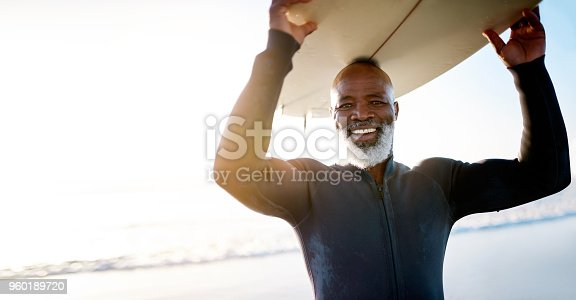 Shot of a mature man carrying a surfboard at the beach