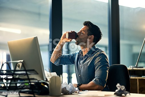 Shot of a young businessman drinking coffee during a late night at work