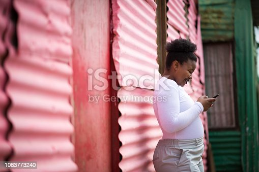 Woman using a cell phone in the townships of South Africa