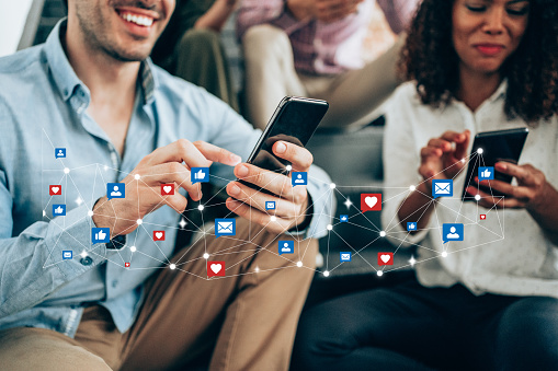 Multi-ethnic group of young people sitting on stairs and using smartphones. Young smiling man receives notifications on smart phone. Social media and digital online concept. Social media and people network technology concept.