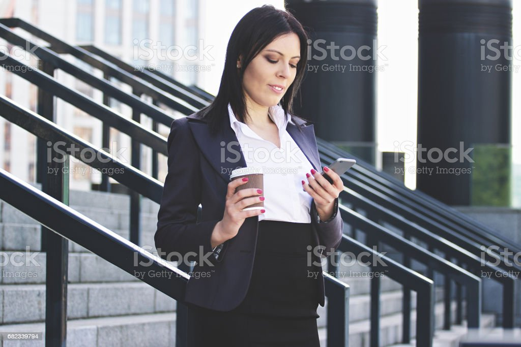 Staying connected. Portrait of beautiful young business woman looking at smart phone while drinking coffee against office building. royaltyfri bildbanksbilder