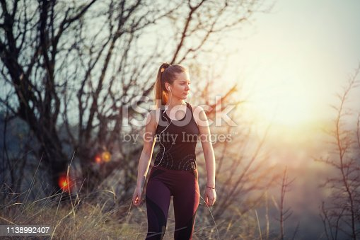 Young female runner staying fit and healthy and looking with motivated on sunset light.