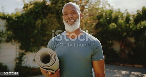 Cropped portrait of a happy senior man standing alone before a yoga session in his back garden