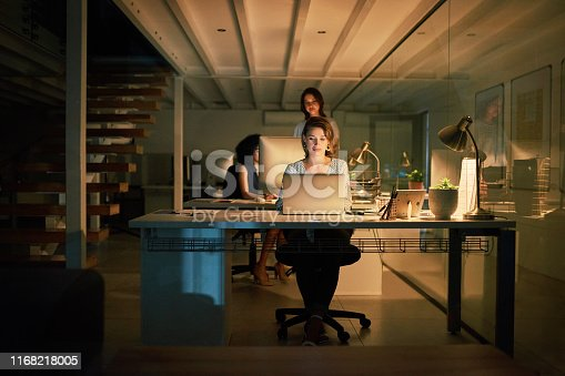 Full length shot of an attractive young businesswoman using her laptop while her colleagues work behind her late at night