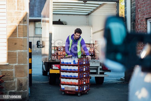 A mid adult Caucasian delivery man pushing bread pallets outdoors, after taking them out of a delivery truck. He is an essential worker during the COVID-19 pandemic.