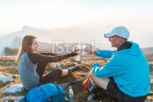 Young man and woman hiking in the mountains. Climbing up the hill with a backpack. Two adults being active. Sunny walk in the nature. Happy couple taking a break,  enjoying the view, eating brunch and talking to each other.