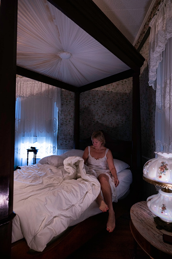 Woman in long white night gown wakes up in a rare 1880 Mallard antique four-poster bed at T'Frere's B&B, a Cajun 1880 Acadian colonial home made of red cypress, Lafayette, Louisiana, USA