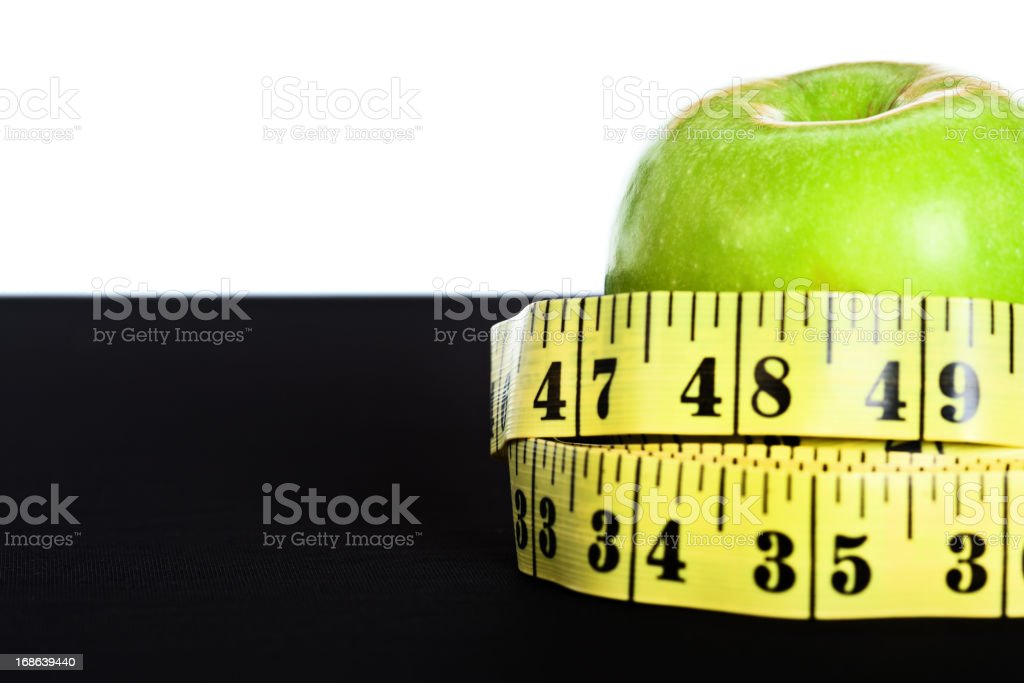 Staying in shape means eating healthily: apple and tape measure stock photo