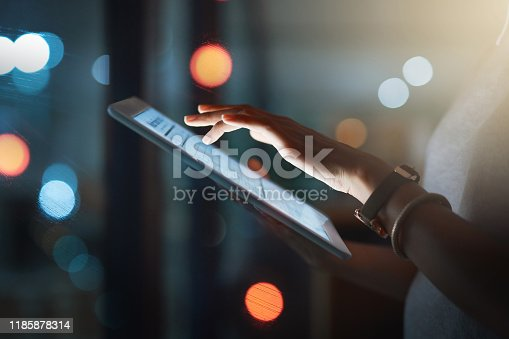 Cropped shot of an unrecognizable businesswoman using a digital tablet while working late
