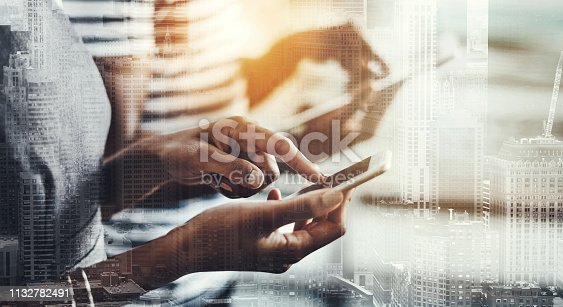 Closeup shot of a group of unrecognizable businesspeople using their digital devices in an office