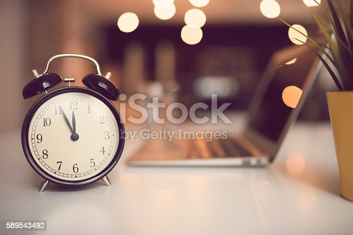 Retro alarm clock and a laptop computer in the background on the table