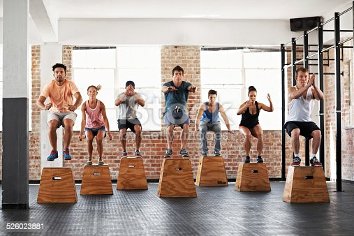 Shot of a group of people jumping onto boxes in a gym class