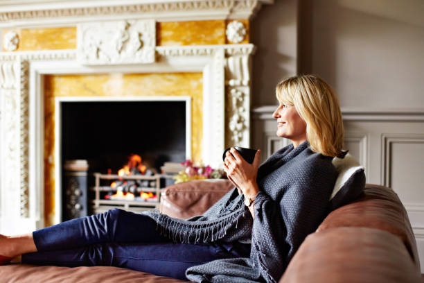Staying warm with a fire and a cup of tea Shot of a mature woman sitting on her sofa drinking tea while wrapped in a blanket wrapped in a blanket stock pictures, royalty-free photos & images