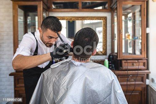 Barber shaving his customer's beard