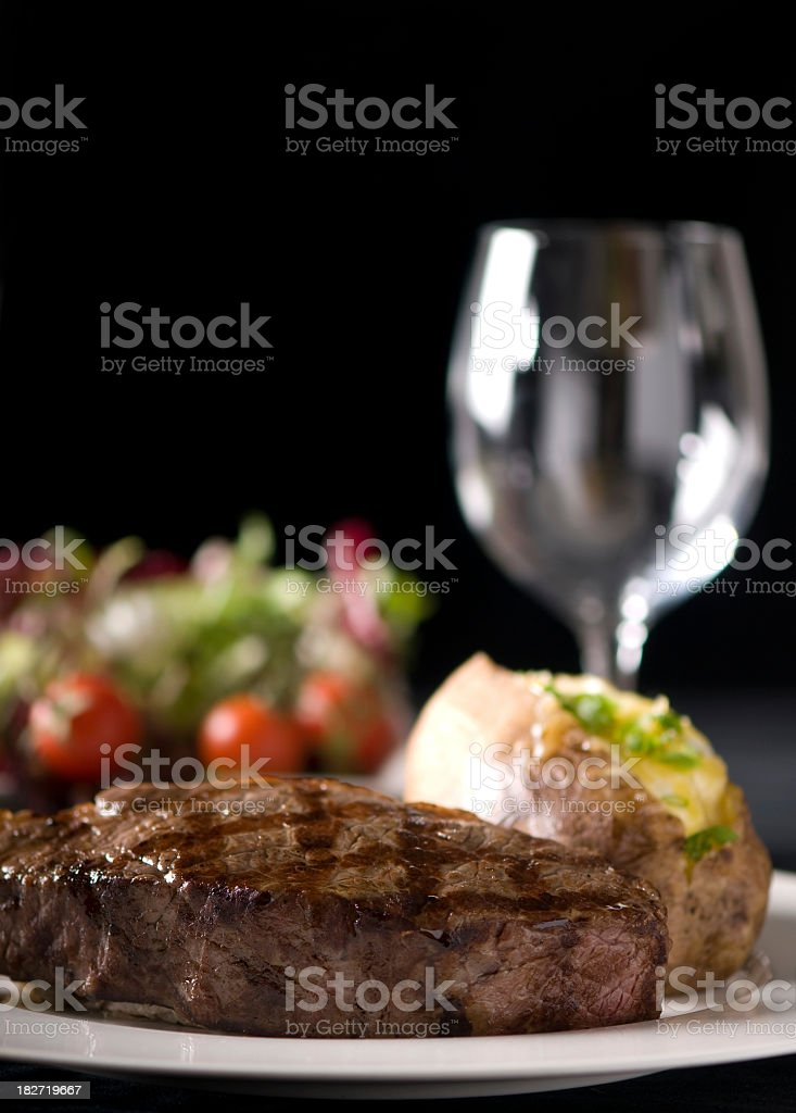 Steak and baked potato in front of empty wine glass royalty-free stock photo