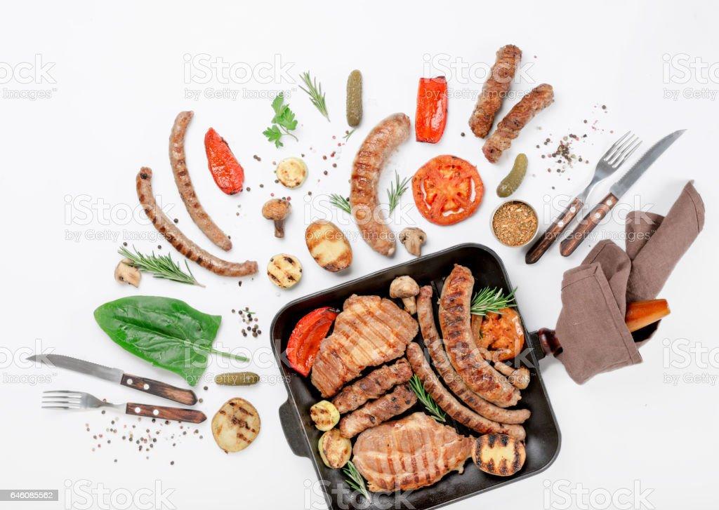 Filete y diferentes embutidos y verduras a la plancha sobre fondo blanco en la cacerola de la parrilla de hierro fundido - foto de stock