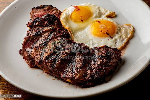Steak and eggs. Traditional classical American diner or French Bistro brunch item, steak and eggs with tots. Angus steak served medium rare with fried eggs and crispy seasoned home fries.