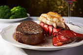 A juicy steak next to a succulent lobster in a white fancy restaurant. There is a plate of blurry broccoli in the background, and this delicious meal is paired with a red wine in a wine glass shown to the right. There is light in the background bokeh into octagons.