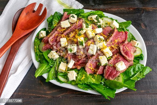 Spinach and fresh herb salad topped with rare flank steak strips, marinated feta cheese cubes, and lemon zest