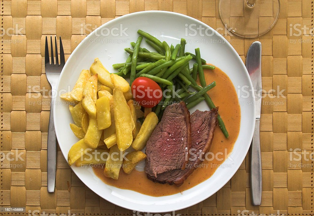 Steak and vegetable dinner on a woven placement royalty-free stock photo