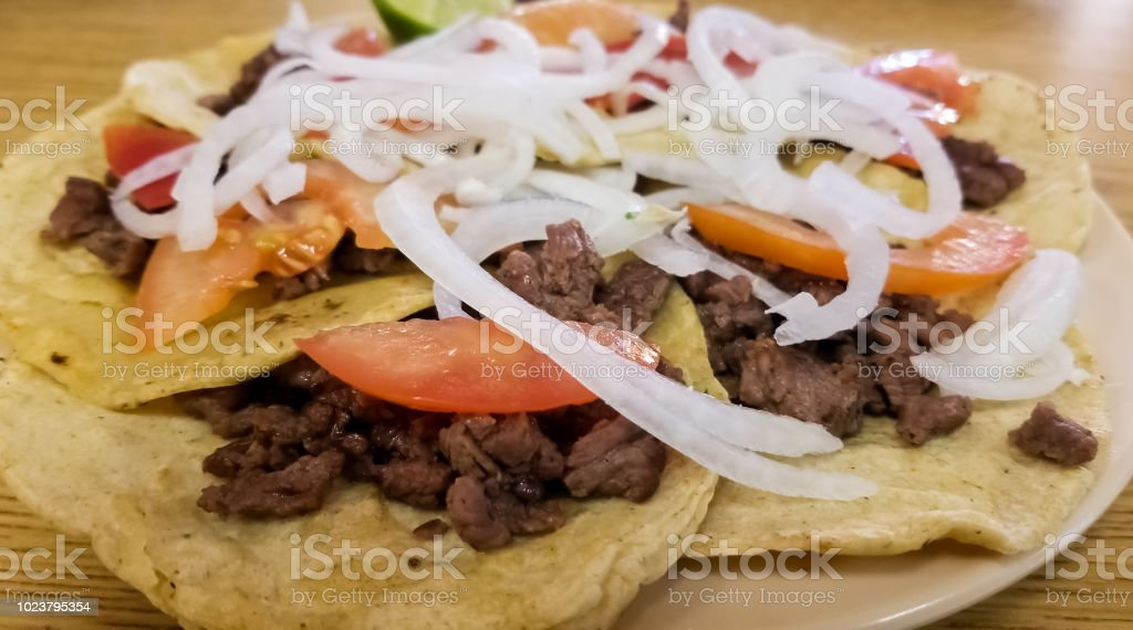 Steak bistec taco  with onion, tomato, red sauce, avocado over Mexican tortilla stock photo