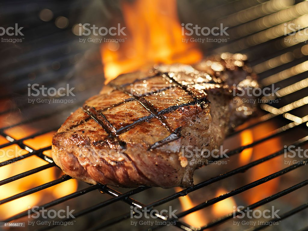 steak cooking on grill with flames stock photo
