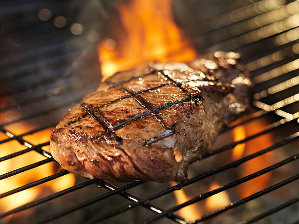 steak cooking on grill with flames - strip steak stockfoto's en -beelden