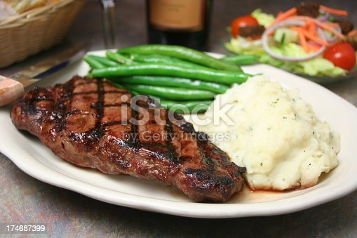 Steak served with mashed potatoes, green beans and a salad.