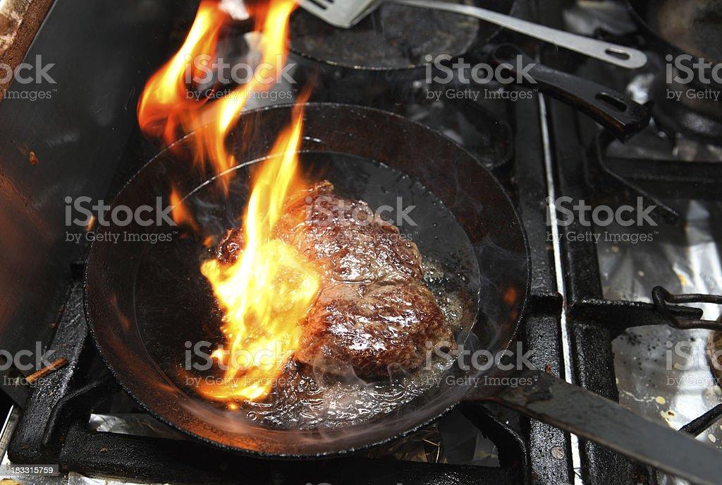 Steak in frying pan on fire stock photo