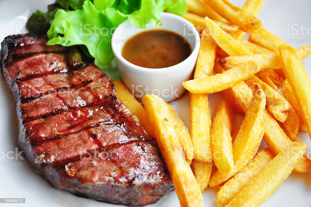 Steak meal with lettuce, french fries and sauce stock photo