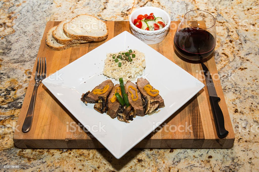 Steak Medallions with Salad, Wine, and Potatoes stock photo