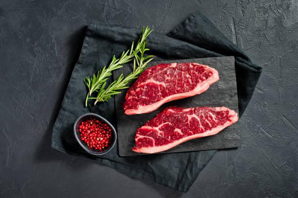 steak of marbled beef black angus. black background, top view. - beef angus imagens e fotografias de stock
