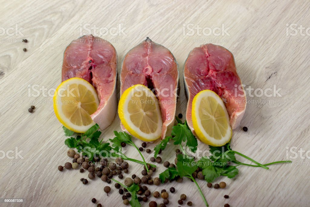 Steak of tuna, lemon, sea salt, pepper, fresh sprouts of greens. stock photo